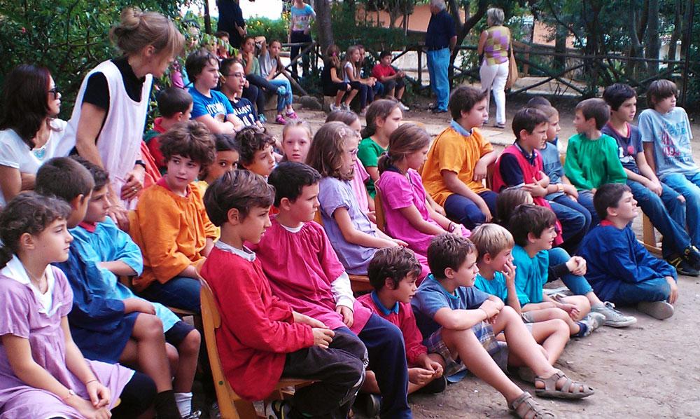Una classe assiste ad una recita in giardino
